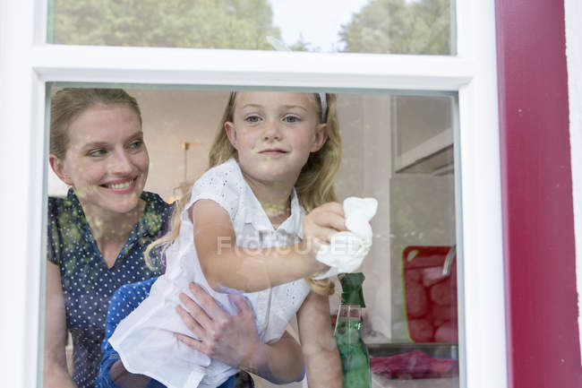 Mother and daughter cleaning window — Stock Photo