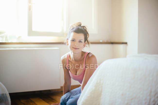 Porträt von Mitte Erwachsene Frau kniet auf dem Boden Schlafzimmers — Stockfoto