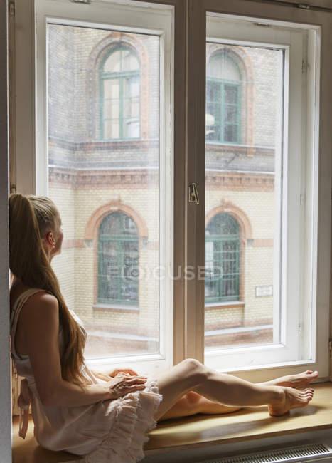 Милая взрослая женщина, сидящая на подоконнике и выглядывающая в окно — стоковое фото