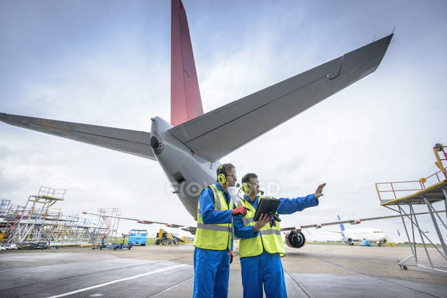 Бортинженеры осматривают реактивные самолеты на взлетно-посадочной полосе — стоковое фото