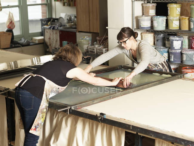 Women hand-printing textile in workshop — Stock Photo
