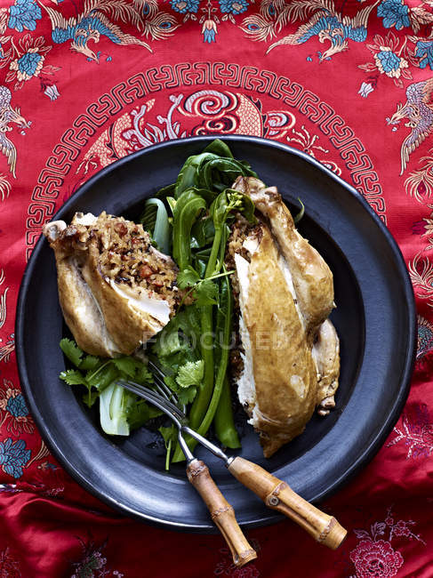 Still life of Beggars Chicken with lotus leaf and greens — Stock Photo