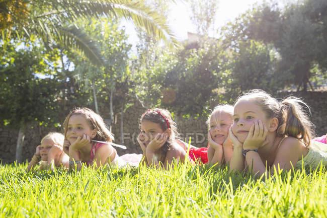 Cinco meninas que encontram-se em uma fileira no jardim com os queixos nas mãos — Fotografia de Stock