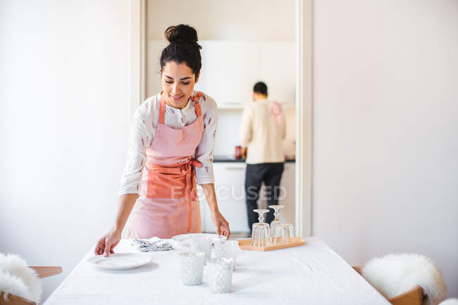 Young housewife wearing apron laying dining table — Stock Photo