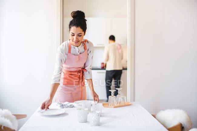 Jeune femme au foyer, portant tablier portant la table à manger — Photo de stock