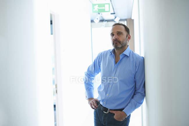 Homme mûr, appuyé contre le mur dans le couloir — Photo de stock