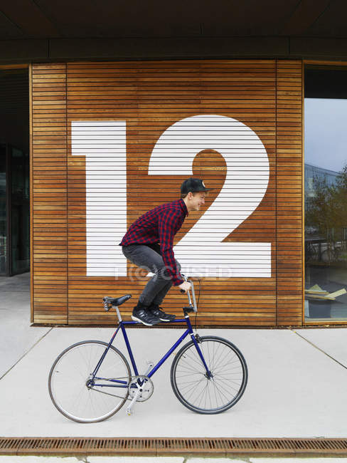 Urban cyclist balancing on bicycle in front of numbered wooden wall — Stock Photo