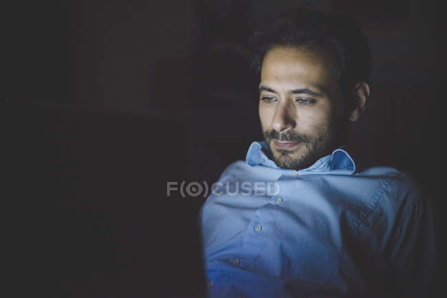 Young man leaning back looking down illuminated by laptop computer screen — Stock Photo