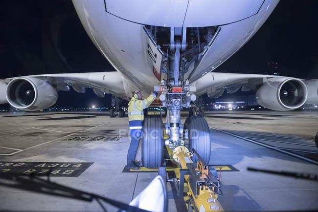 Ingeniero jefe inspeccionando aviones A380 en pista en el aeropuerto por la noche - foto de stock