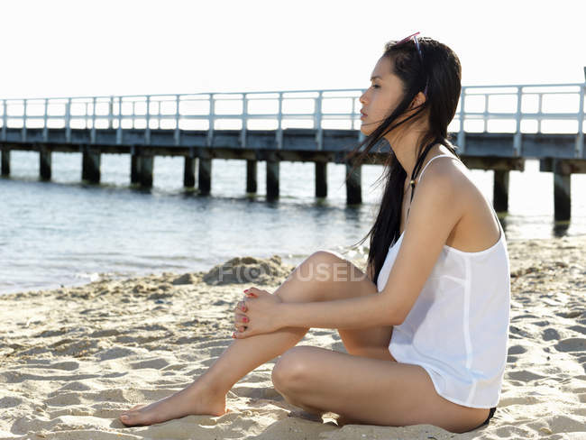 Young woman sitting looking away beach, Port Melbourne, Melbourne, Victoria, Australia — Stock Photo