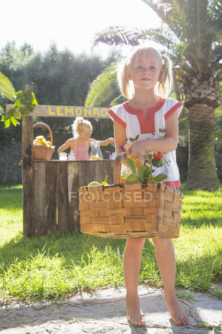 Portrait de fille portant panier de citrons devant le stand de limonade — Photo de stock