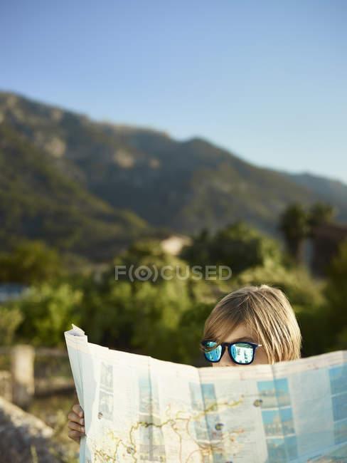 Menino de óculos de sol olhando para um mapa, Maiorca, Espanha — Fotografia de Stock