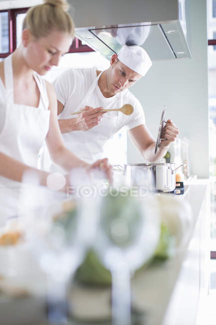Male and female chefs cooking on hob in commercial kitchen — Stock Photo
