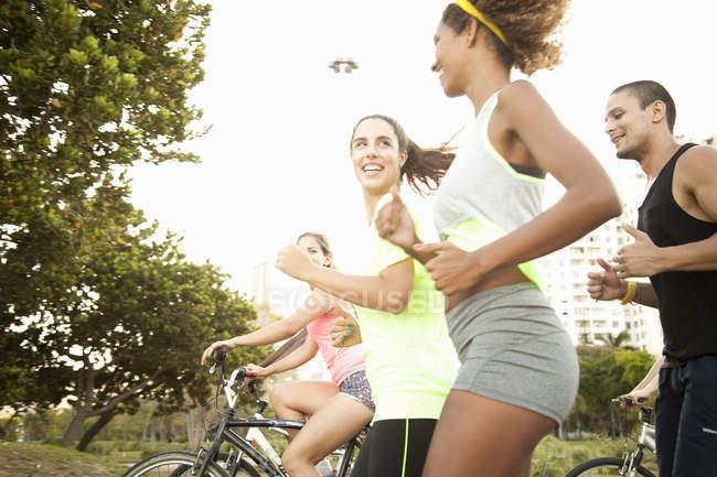 Amici adulti che corrono e pedalano nel parco — Foto stock
