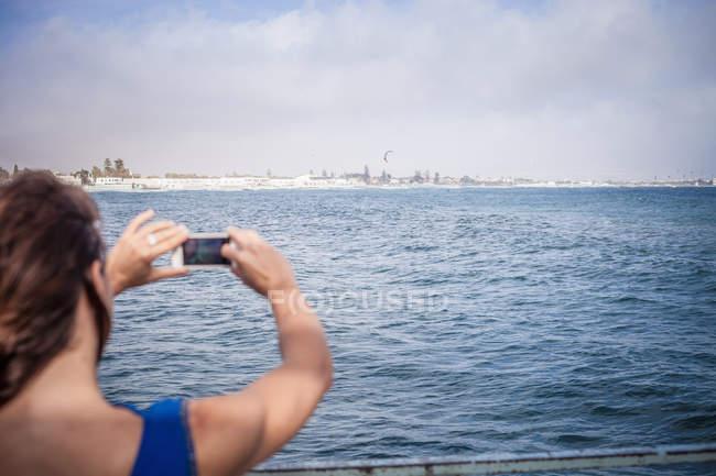Задній вид жінки, яка фотографує морський вид на смартфон. — стокове фото