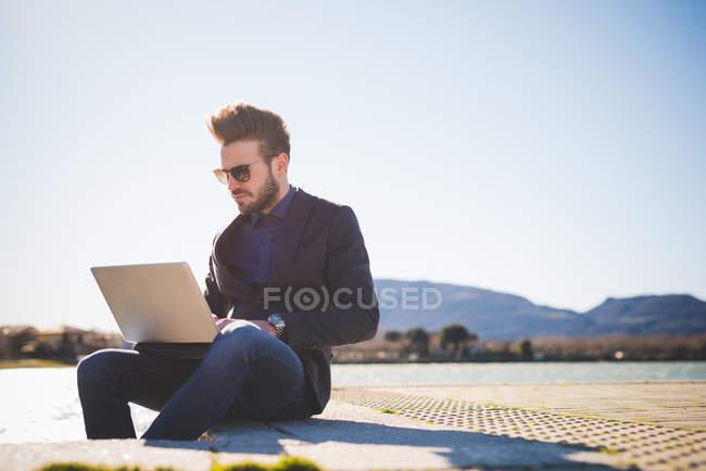 Jovem usando laptop no passo à beira do lago — Fotografia de Stock