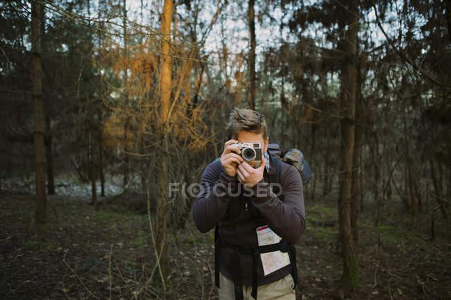 Escursionista maschio che fotografa con macchina fotografica digitale nel bosco — Foto stock