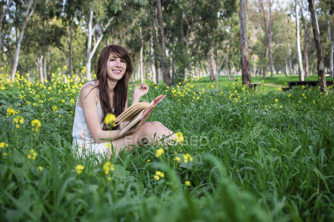 Young woman sitting in forest, reading book — Stock Photo