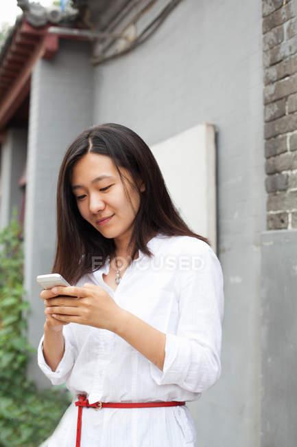 Joven mujer asiática mirando el teléfono móvil - foto de stock