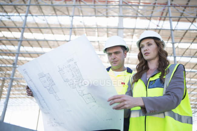 Site manager and architect looking down at blueprint on construction site — Stock Photo