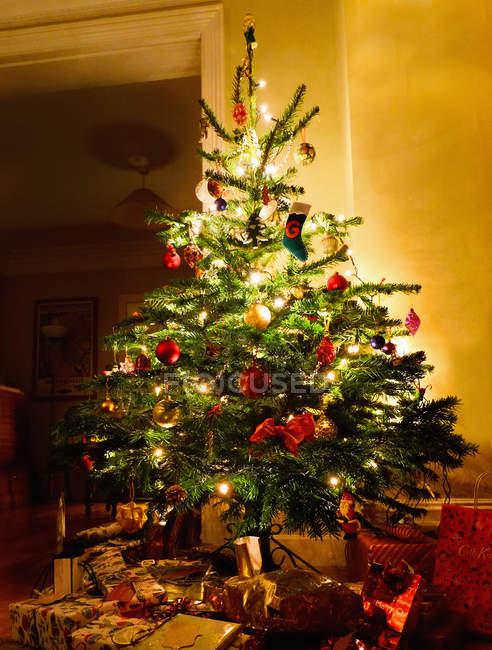 Iluminación árbol de Navidad con los regalos debajo de - foto de stock