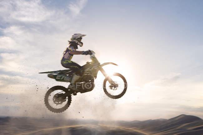 Силуэт молодого мотокросса, прыгающего по грязевой трассе — стоковое фото