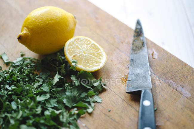Chopped parsley and lemon with knife on wooden board — Stock Photo