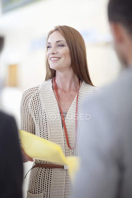 Бизнесвумен и мужчина с документами в атриуме конференц-центра — стоковое фото
