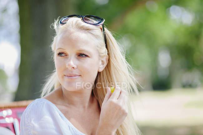 Retrato de una joven rubia de pelo largo con gafas de sol en la cabeza mirando hacia otro lado sonriendo - foto de stock