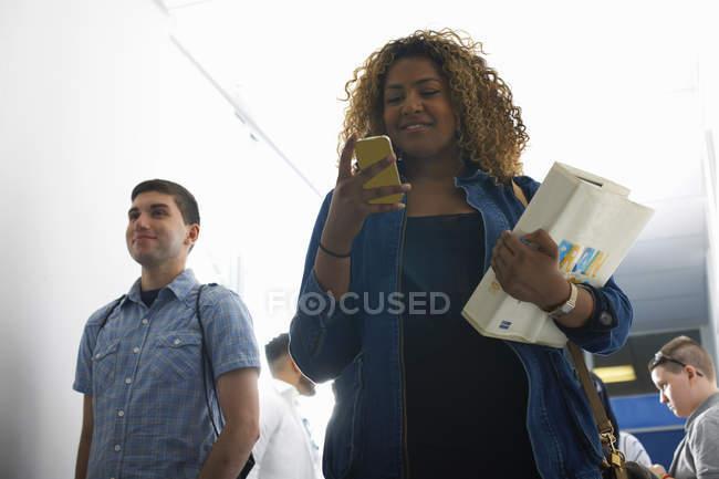 Adolescente lisant un message texte sur smartphone dans un couloir universitaire — Photo de stock