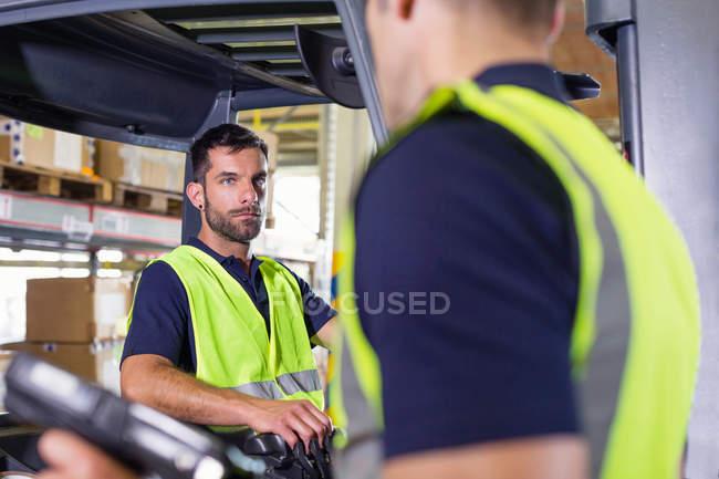 Supervisore che istruisce il conducente del carrello elevatore nel magazzino di distribuzione — Foto stock
