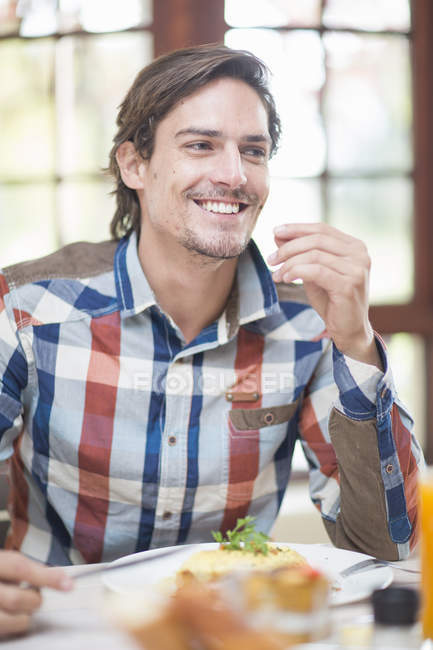Mid adult man sitting at restaurant table — Stock Photo