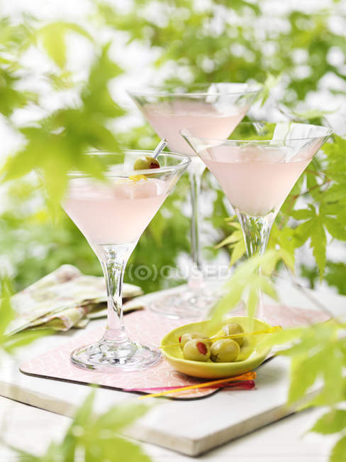 Three glasses of pink martini cocktails with green olives — Stock Photo