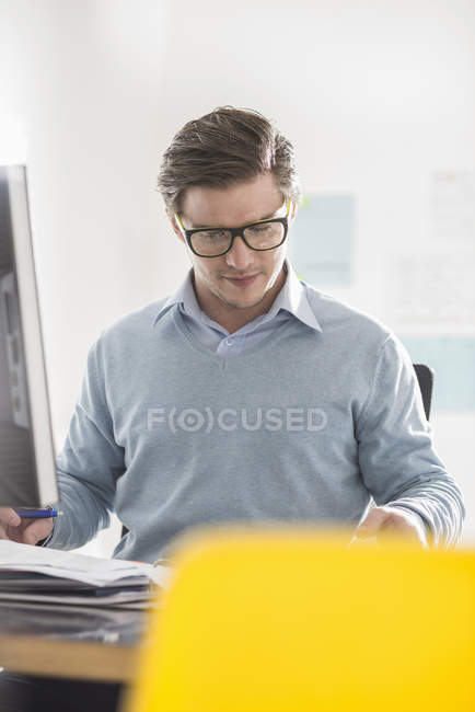 Young businessman doing paperwork at office desk — Stock Photo