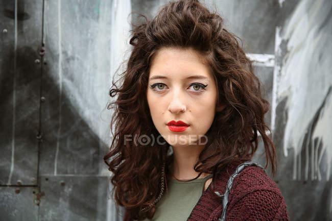 Ritratto di giovane donna contro parete grigia grunge — Foto stock