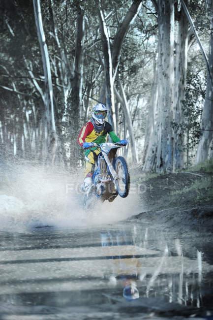 Молодой мотокросс едет по грунтовой луже в лесу — стоковое фото