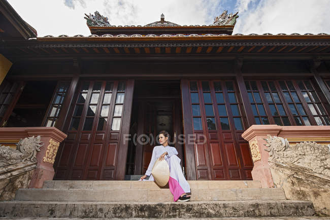 Low angle view of mid adult woman wearing ao dai dress with conical hat sitting on steps in front of imperial palace doorway looking away, Hue, Vietnam — Stock Photo