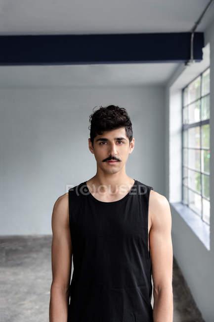 Porträt eines jungen Mannes in Schwarz, der im Studio steht — Stockfoto