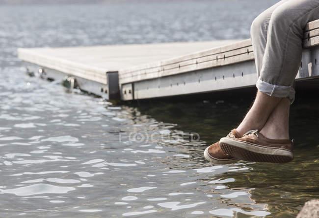 Beine des jungen Mannes baumelte pier — Stockfoto