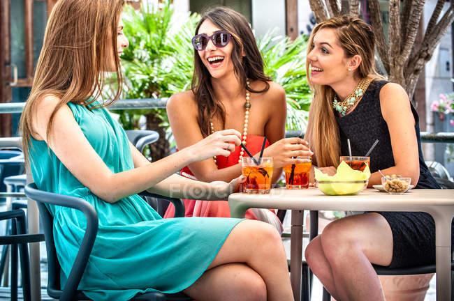 Três jovens amigas da moda tomando coquetéis no café da calçada, Cagliari, Sardenha, Itália — Fotografia de Stock