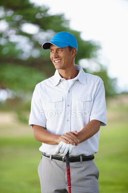 Golfeur portant le gant de golf et de baseball cap holding golf club sourire loin à la recherche — Photo de stock