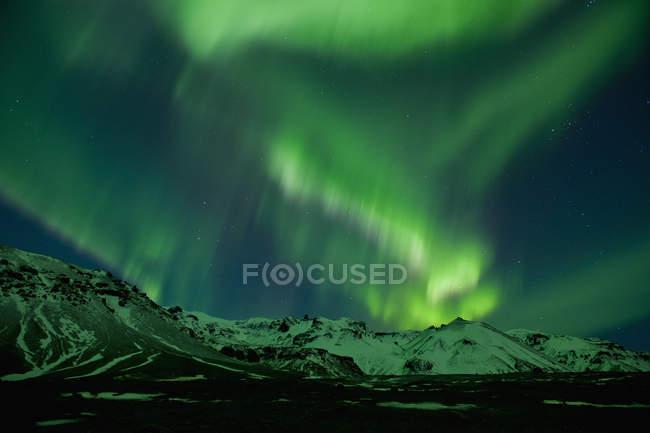Полярне сяйво над snowcapped гори вночі — стокове фото