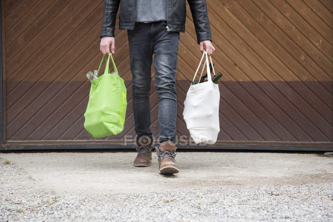 Teenage boy carrying reusable shopping bags full of empty bottles for recycling — Stock Photo