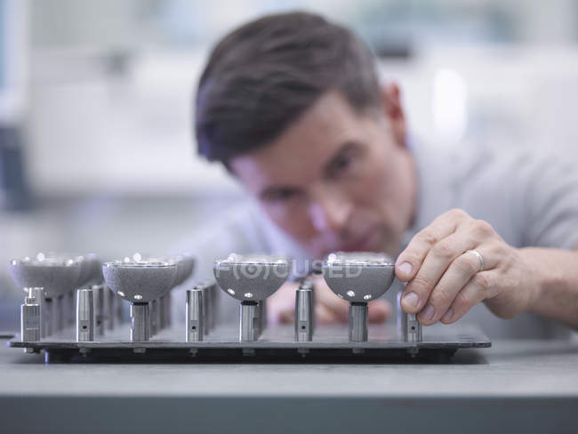 Engineer inspecting artificial hip joint parts in quality control department in orthopaedic factory — Stock Photo