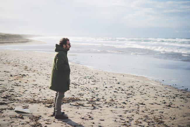 Mid adult man looking out at sea on windy beach, Sorso, Sassari, Sardinia, Italy — Stock Photo