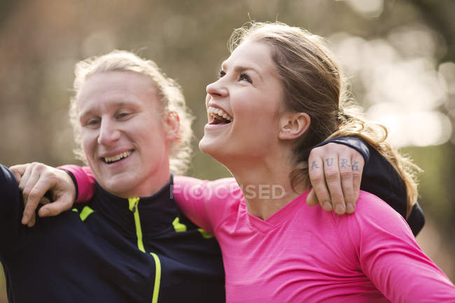 Head and shoulders of couple wearing sports clothing arms around each other looking away smiling — Stock Photo