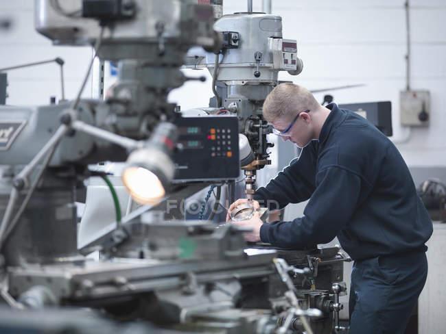 Apprentice engineer on lathe in engineering factory — Stock Photo