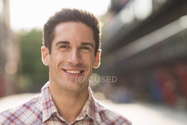 Jovem vestindo camisa marcada, sorrindo — Fotografia de Stock