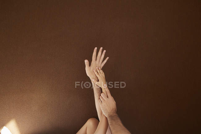 Niño y hombre manos en el otro en el fondo de color - foto de stock