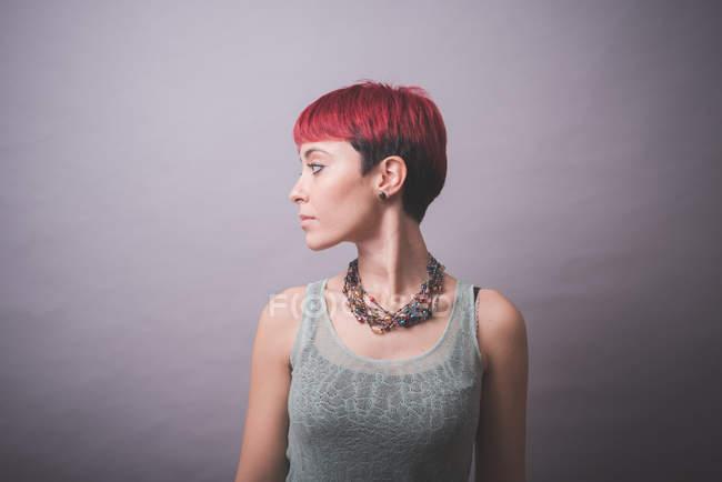 Studio-Porträt der jungen Frau mit kurzen rosa Haaren über die Schulter schauen — Stockfoto
